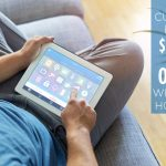 man sitting on couch using a home automation app on his tablet